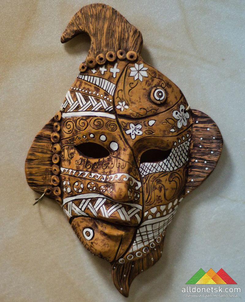 Эта маска, если присмотреться, состоит из двух рыбок - с плавниками, хвостами и чешуей в виде орнамента