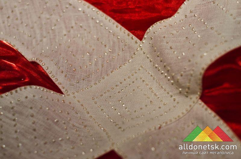 Крест датского флага мерцает застывшими капельками краски